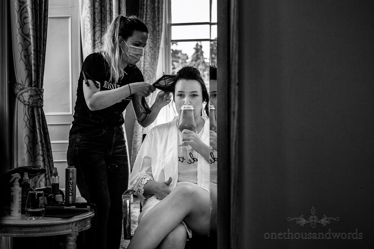Bride drinks wedding morning beer and gives thumbs up during wedding hair styling in mirror
