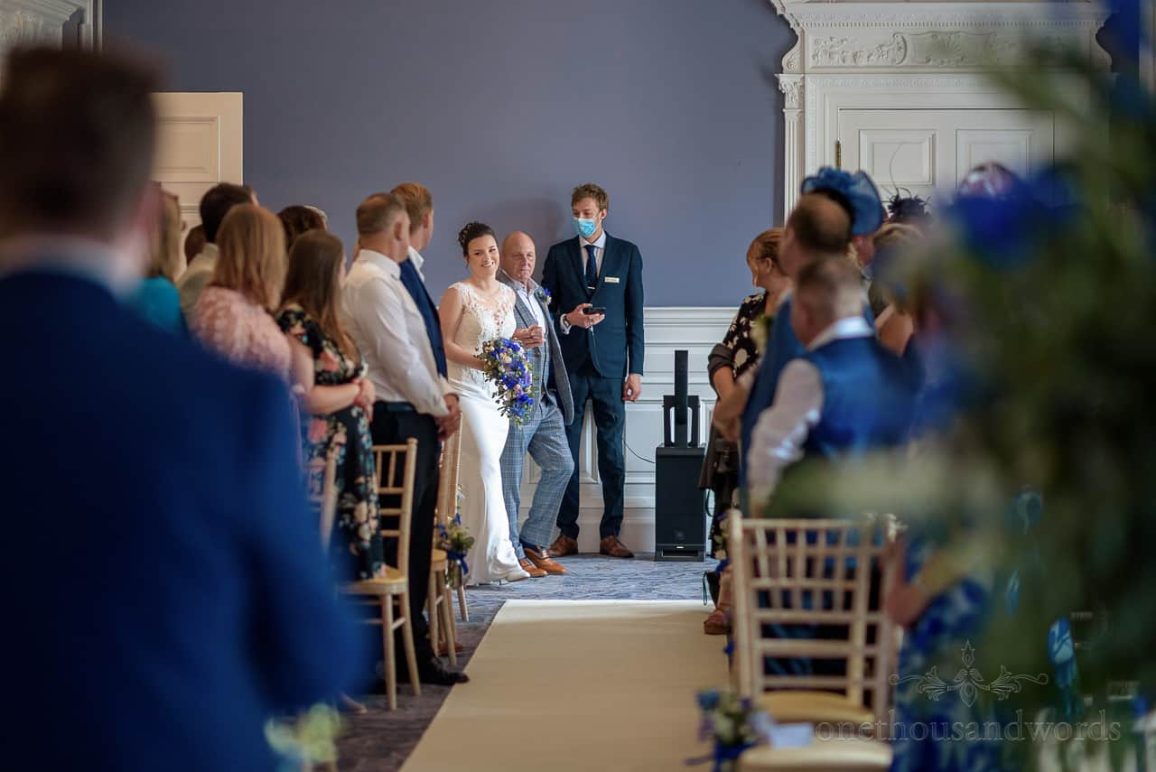 Bride and father enter wedding ceremony aisle at Oakley Hall wedding