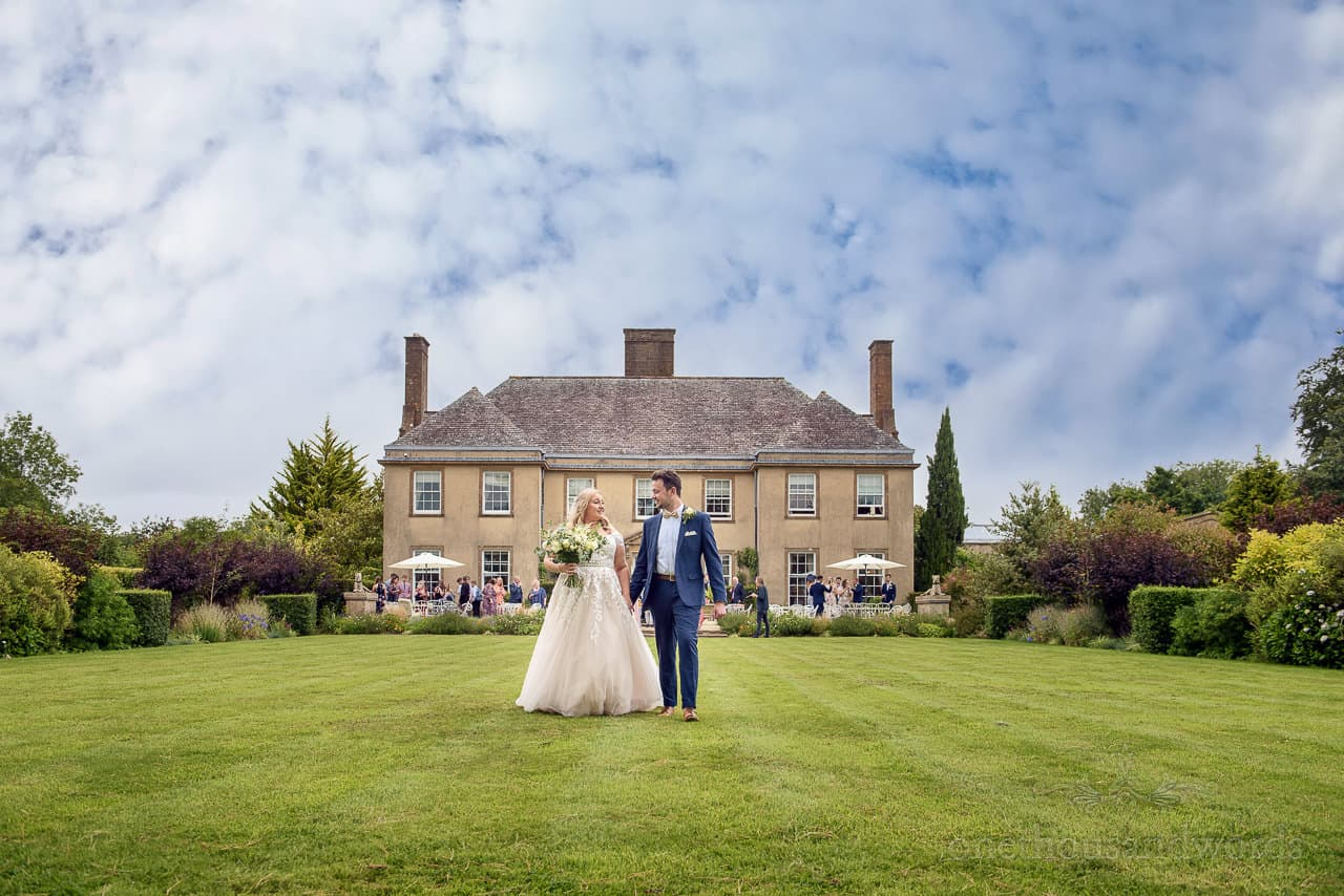 Bride and Groom walk through gardens at wedding at Hethfelton House in Dorset