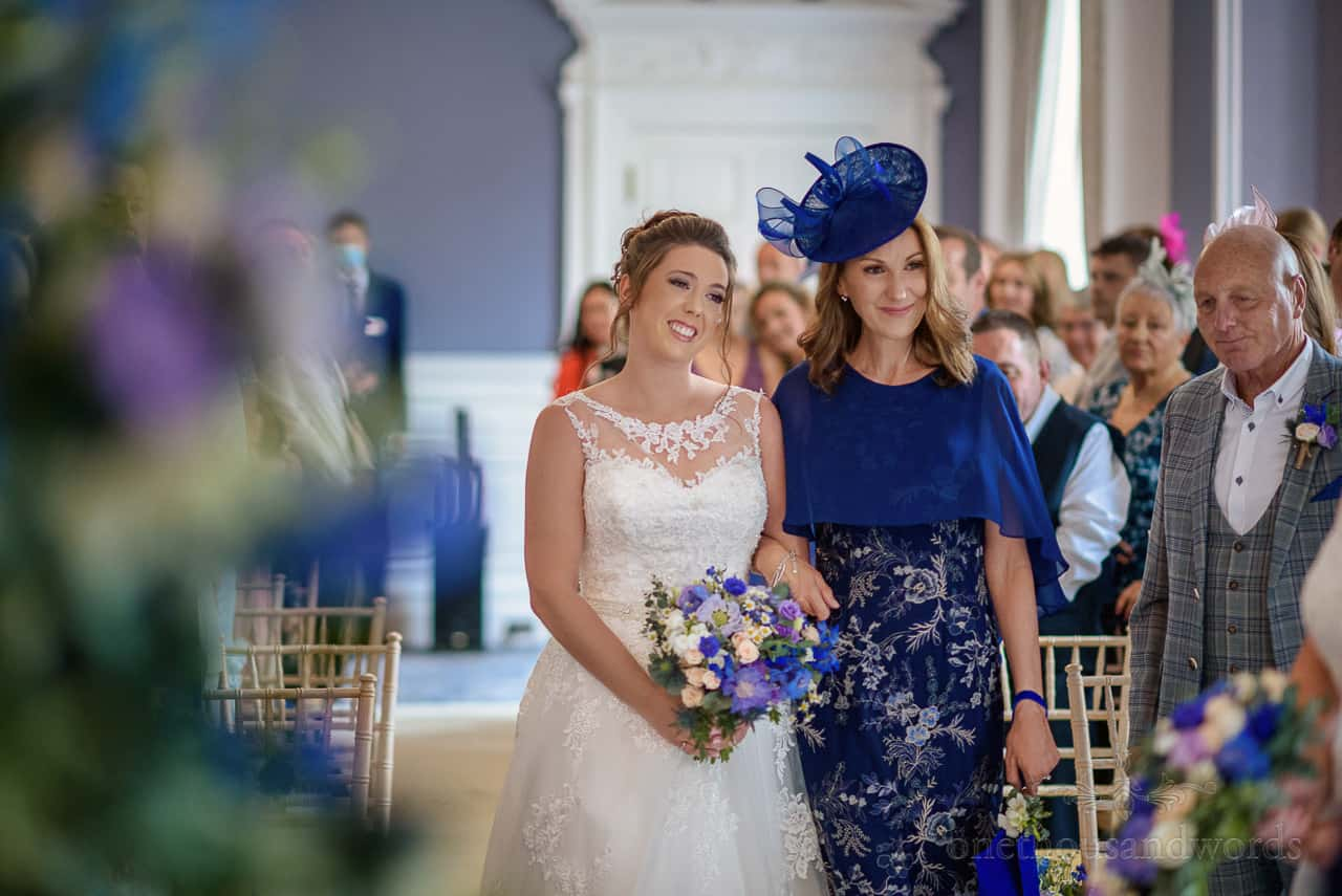 Bride's mother in blue dress walks down aisle at Oakley Hall civil wedding ceremony