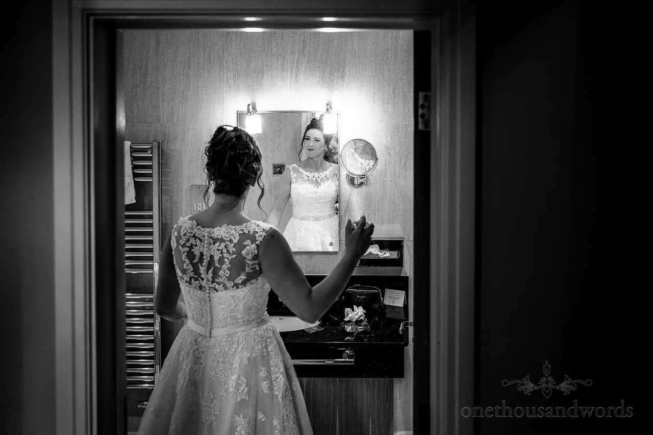 Bride sprays perfume in bathroom mirror on wedding morning