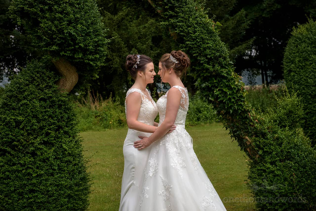 Brides in white wedding dresses kissing in Oakley Hall gardens