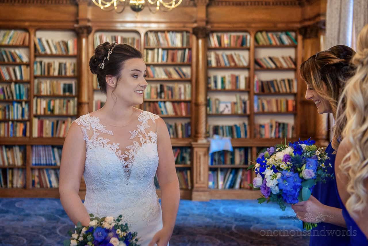Bride in white lace detailed wedding dress laughing with bridesmaids in Oakley Hall library