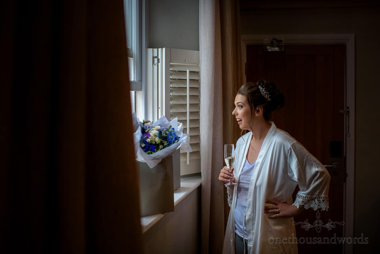 Bride in white silk dressing gown looking through window on wedding morning
