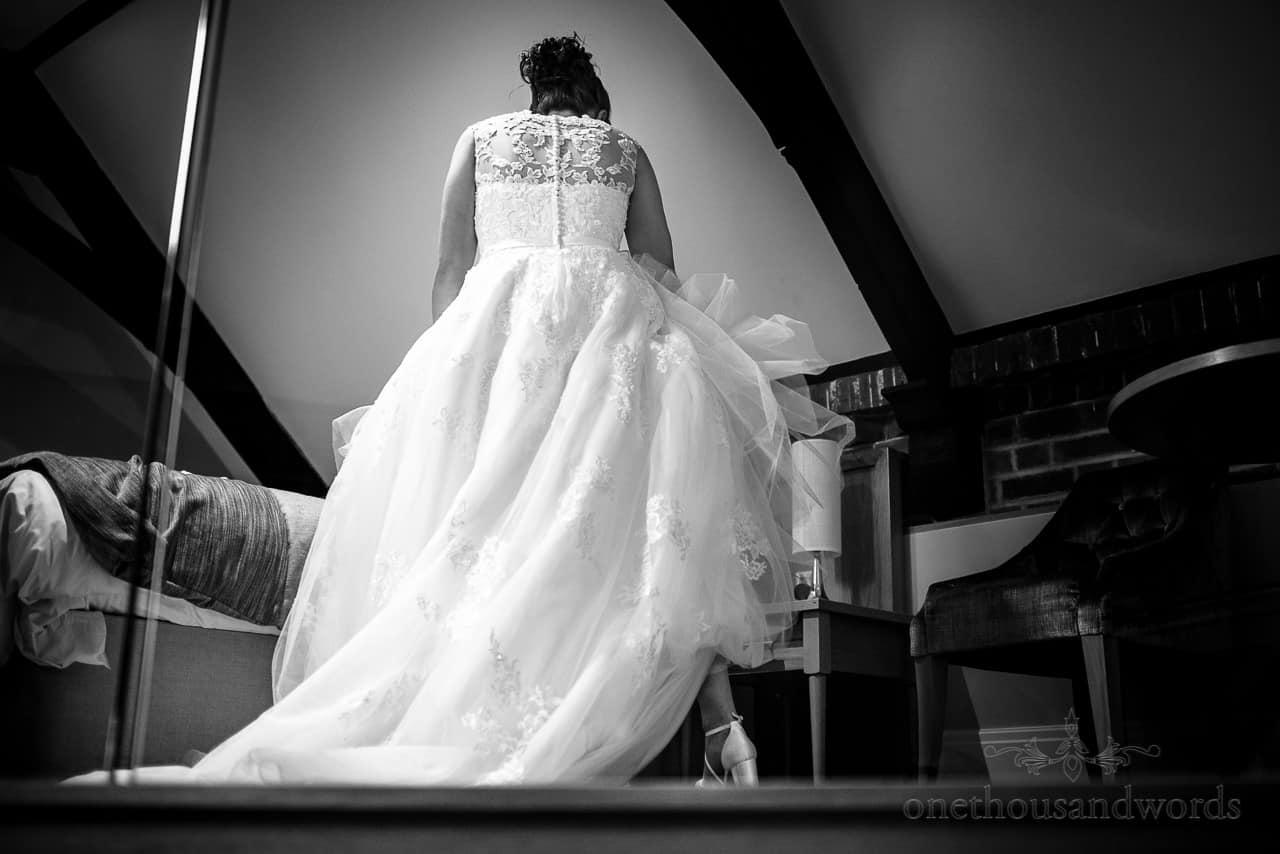 Bride has white wedding dress adjustments at Oakley Hall courtyard balcony