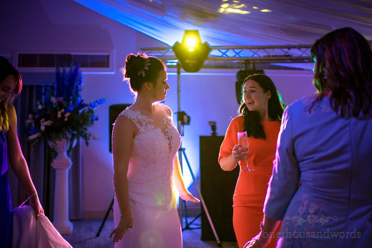 Bride in white wedding dress dancing with wedding guests under coloured disco lighting