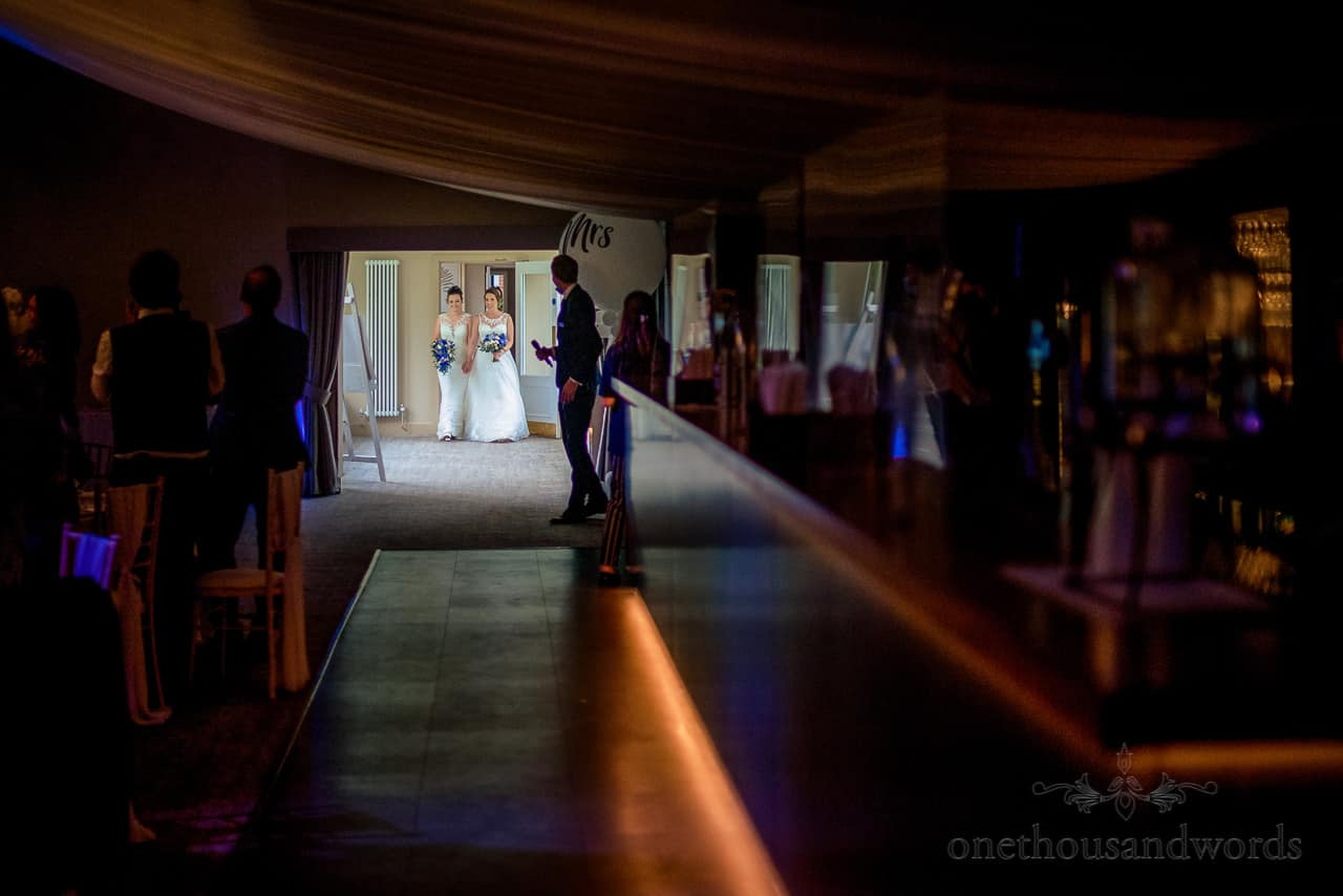 Brides enter wedding pavillion marquee to guests standing ovation at Oakley Hall