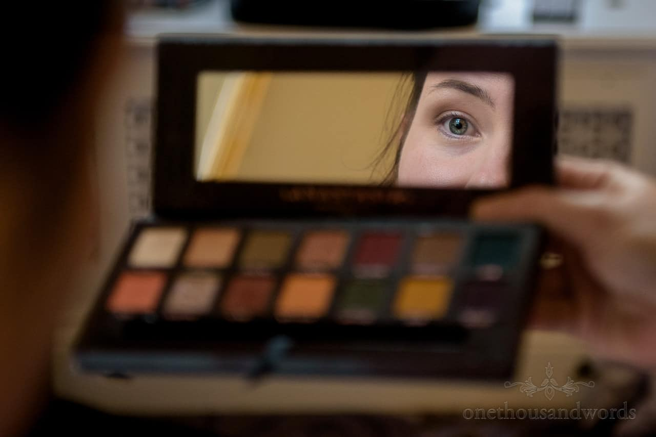 Bride's eye reflected in make up compact mirror