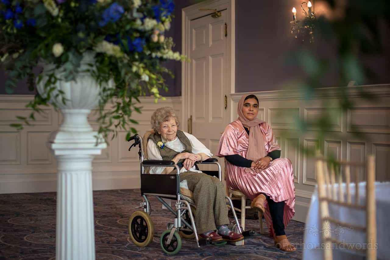 Bride's grandmother in wheelchair with carer positioned to watch wedding ceremony