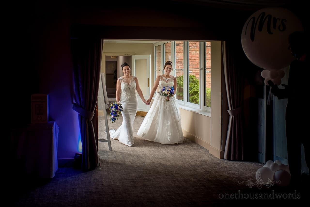 Brides walk hand in hand entering wedding breakfast marquee