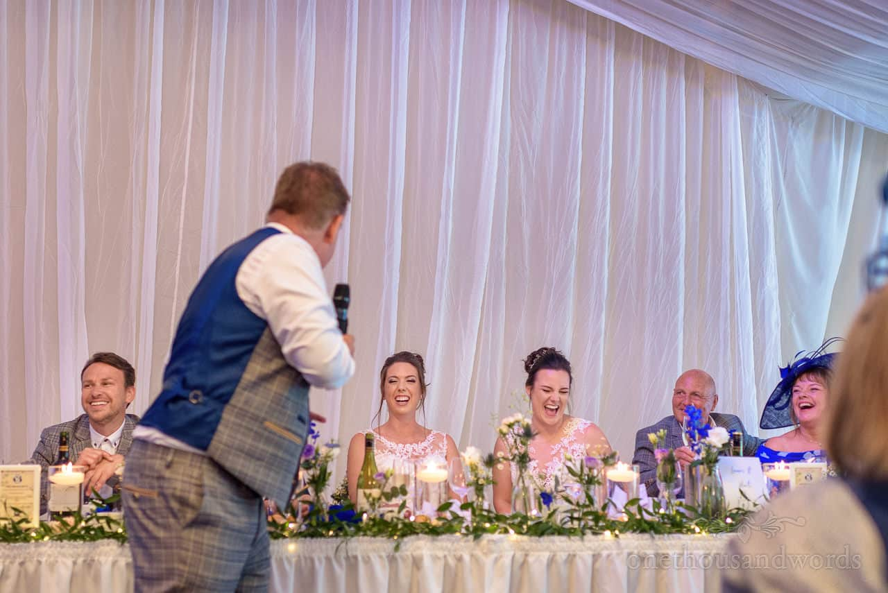Brides laughing at best man's speech in wedding marquee