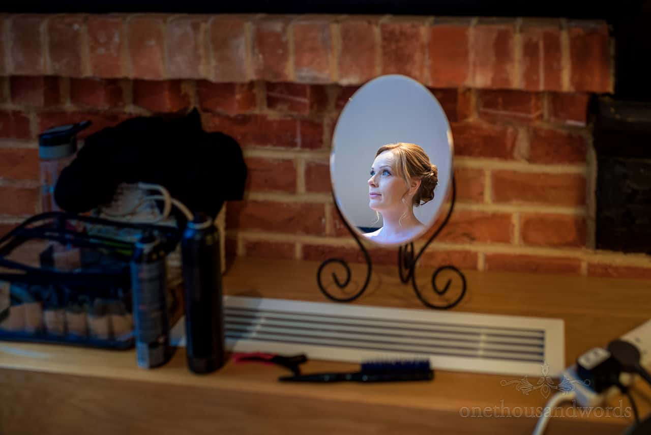 Bridesmaid portrait photo of reflection in make up mirror in front of red brick wall