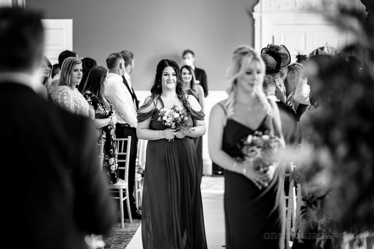 Bridesmaids walk down wedding aisle at Oakley Hall