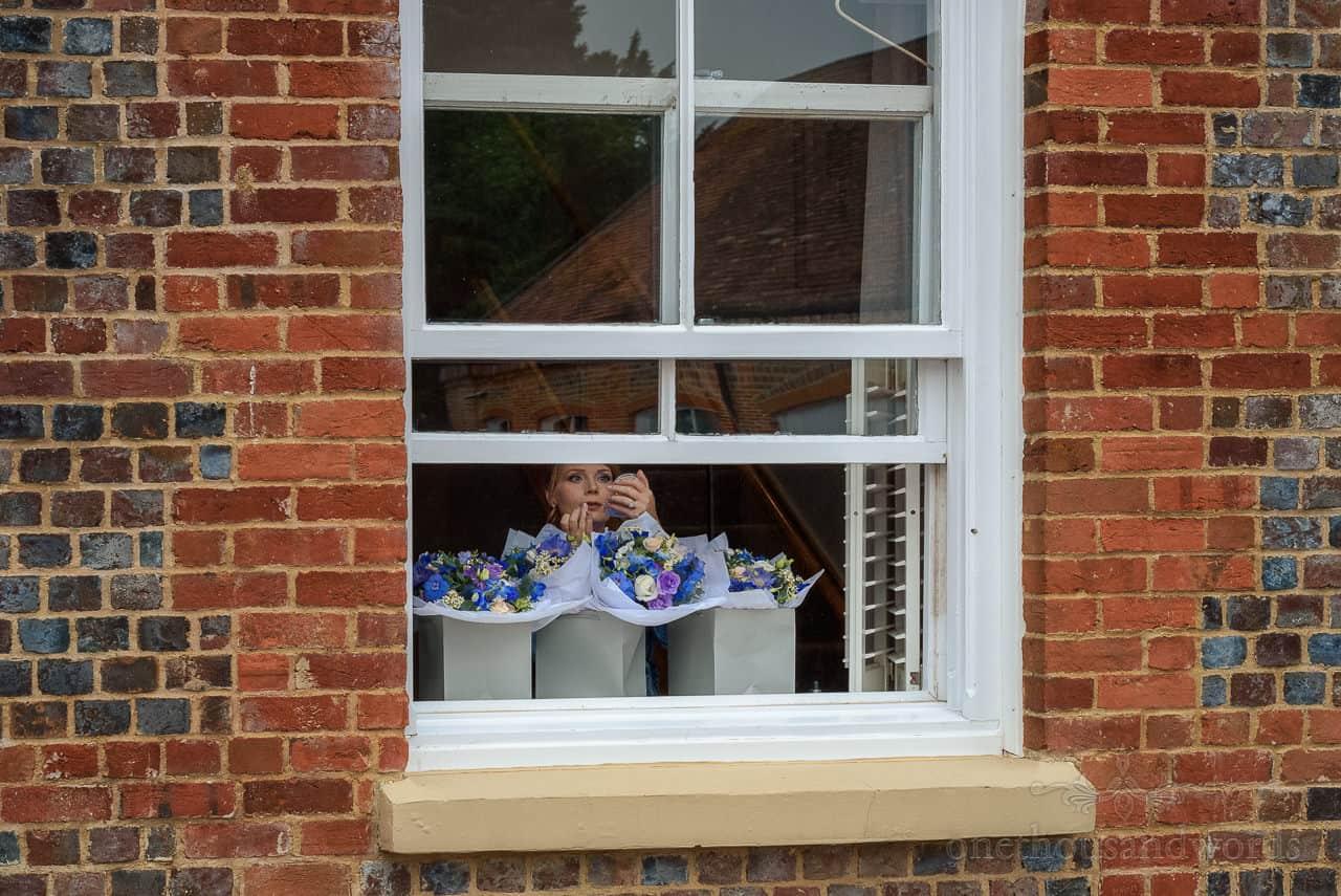 Bridesmaid adjusts wedding makeup in sash window with wedding bouquet flowers