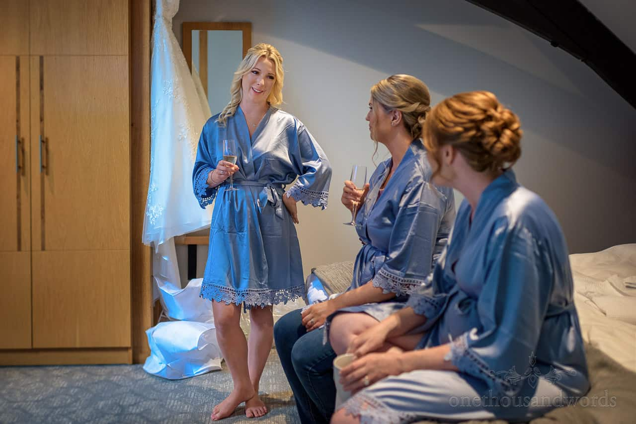 Bridesmaids in blue silk dressing gowns whilst drinking champagne
