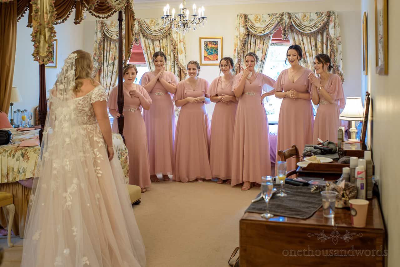 Bridesmaids emotional reactions to bride in wedding dress on wedding morning