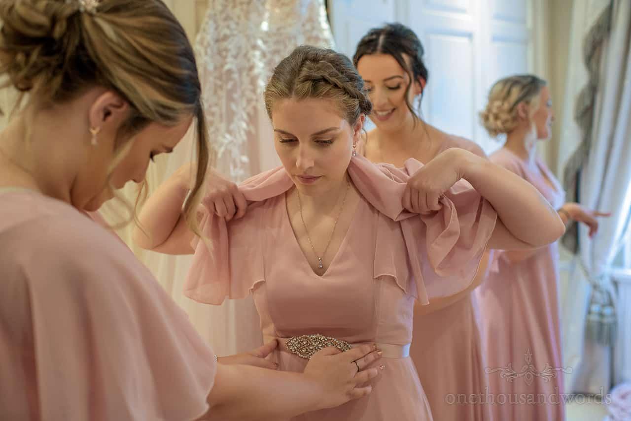 Bridesmaids put on dusty pink bridesmaids dresses