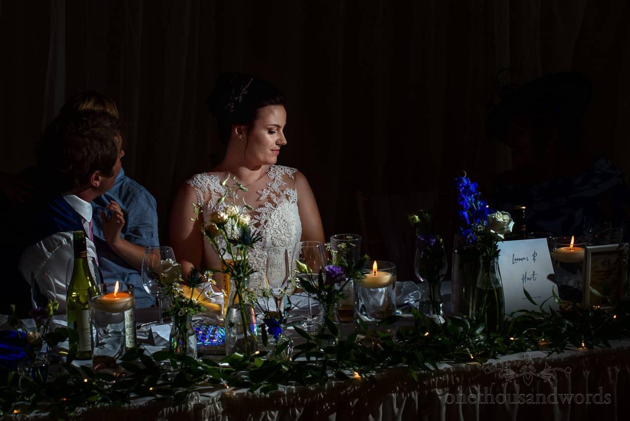 Calm bride portrait photo behind top table at wedding breakfast