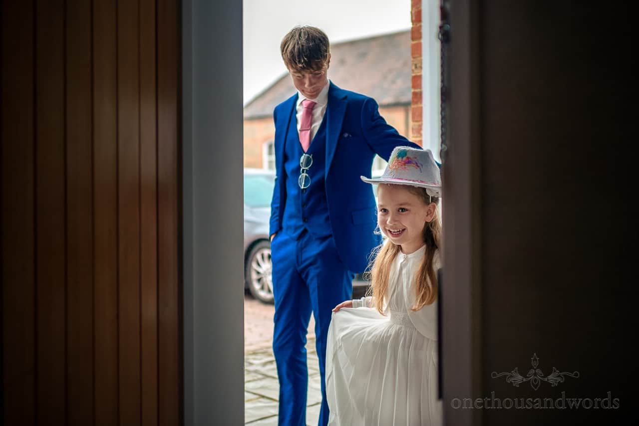 Cute flower girl in white wedding dress wearing cow girl hat on wedding morning at Oakley Hall