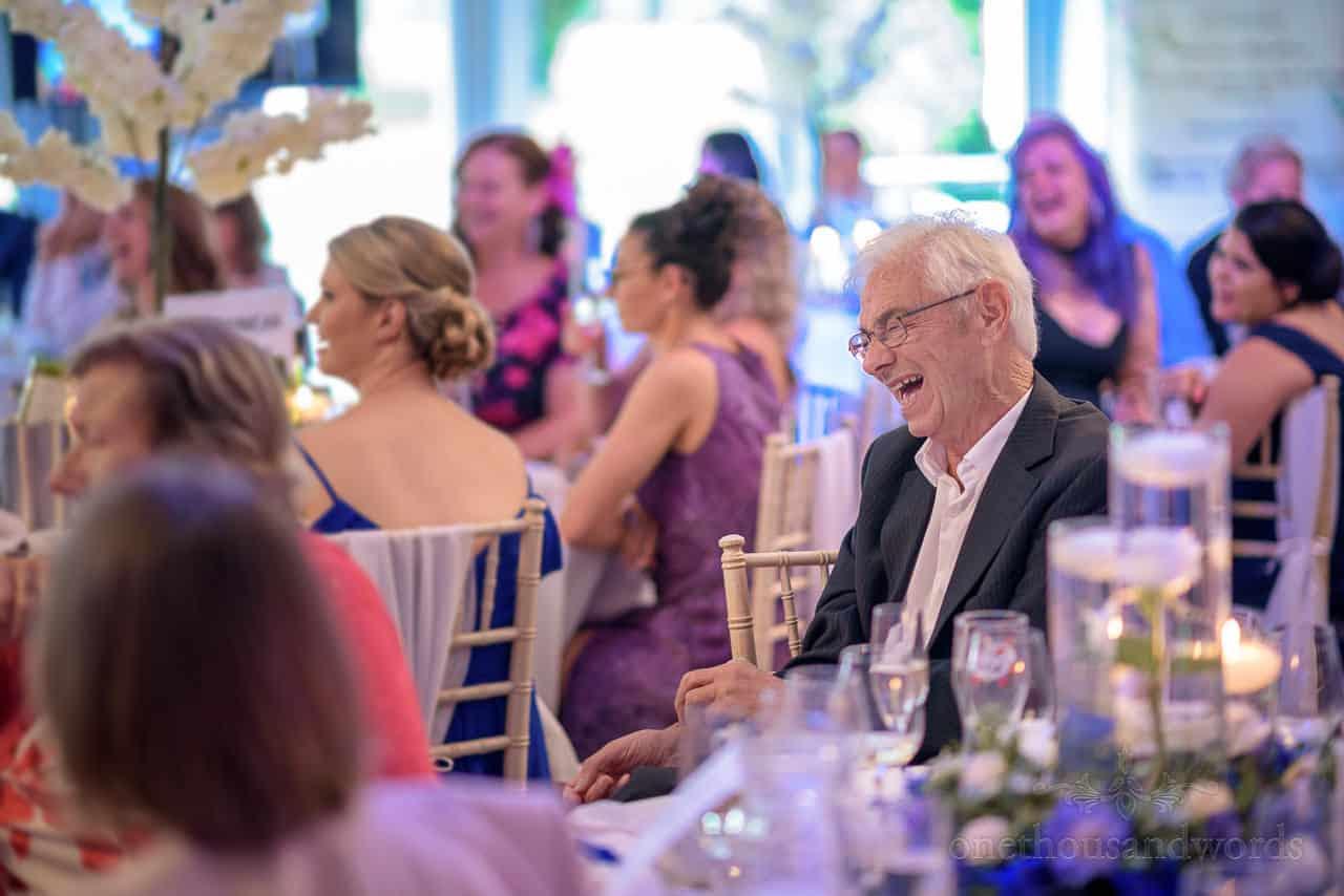 Elderly wedding guest gut laughing at wedding seeches