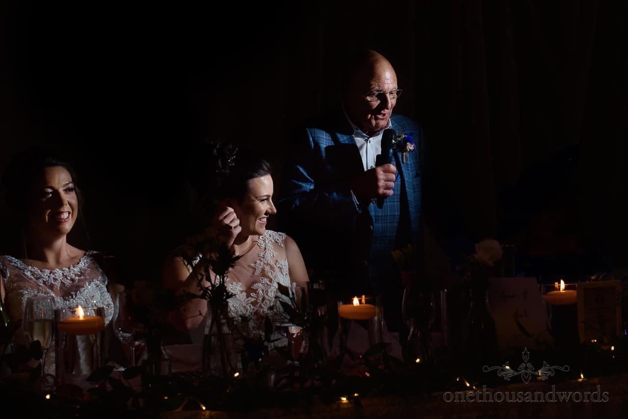 Father of the bride in blue checked suit gives wedding speech behind top table with microphone