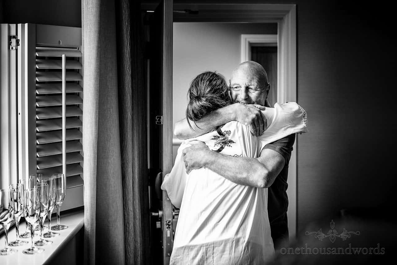 Documentary wedding photo of father hugging bride on wedding morning