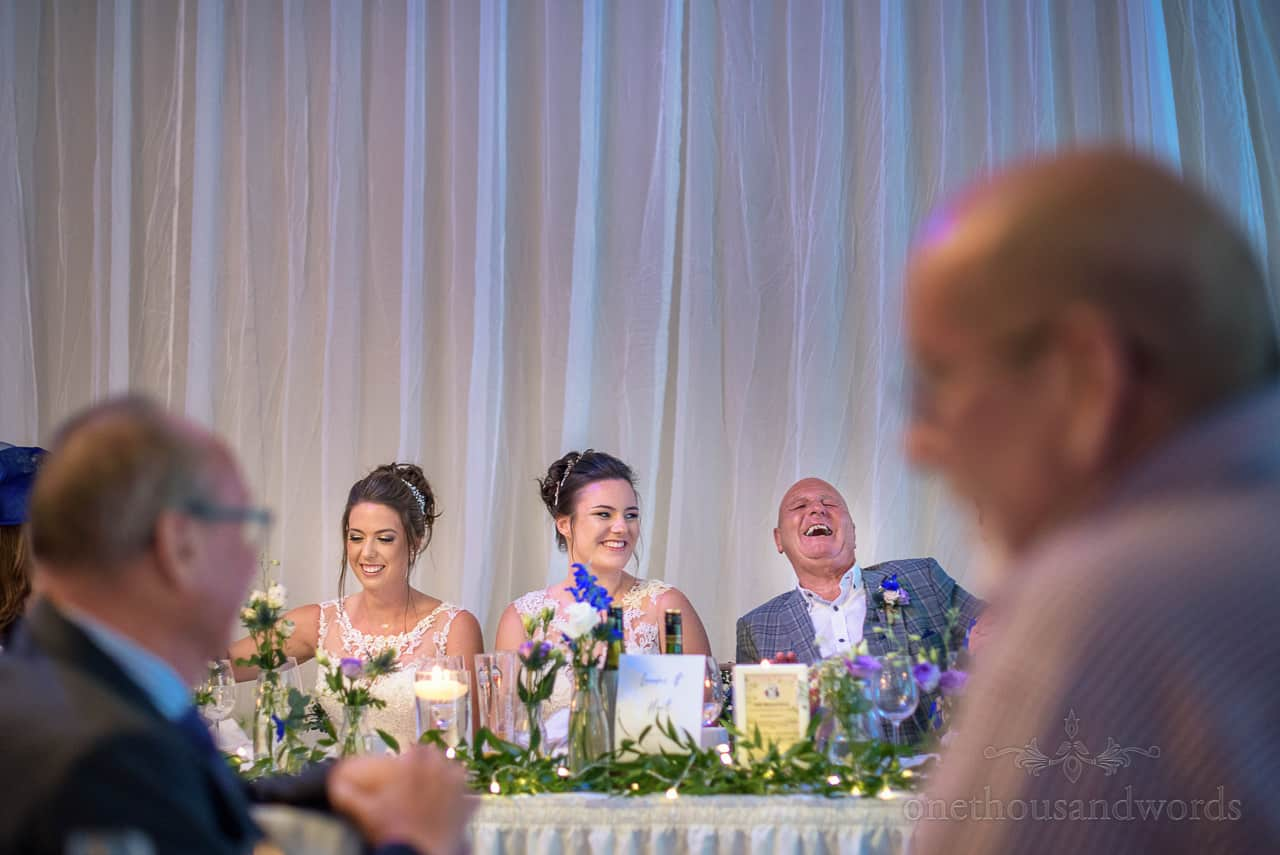 Father of the bride's laughing reaction to wedding speeches at marquee wedding