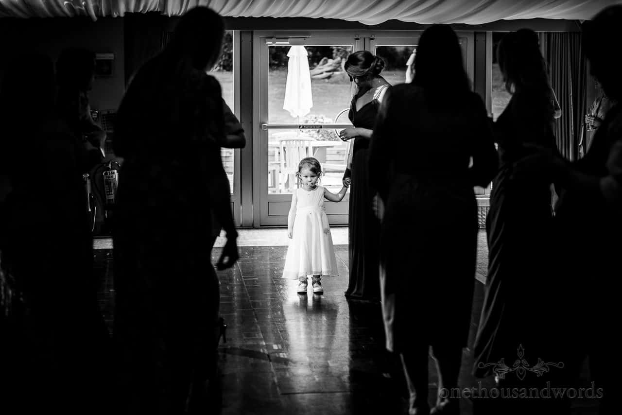 Flower girl with dummy in mouth in wedding marquee with wooden dancefloor