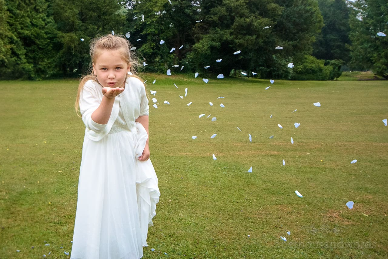 Flower girl in white dress blowing white confetti petals on grass lawns