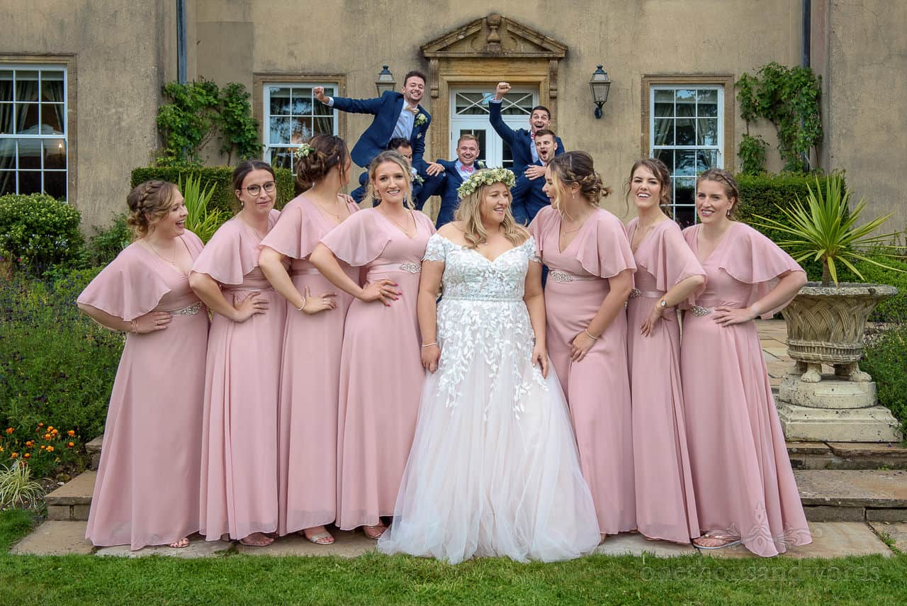 Funny wedding photo of groomsmen photobombing bride and bridesmaids during group photos