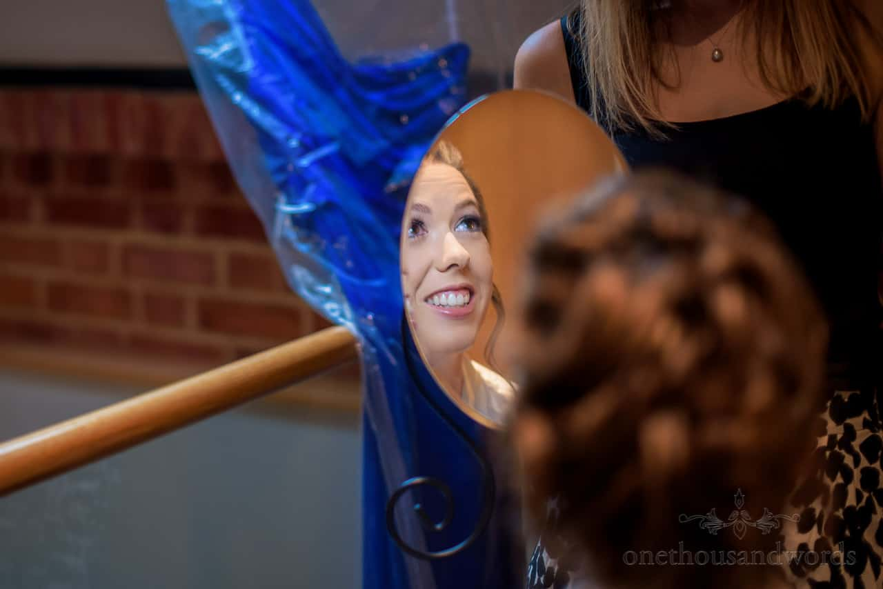 Happy bride's face reflected in wedding makeup mirror in front of blue bridesmaids dress