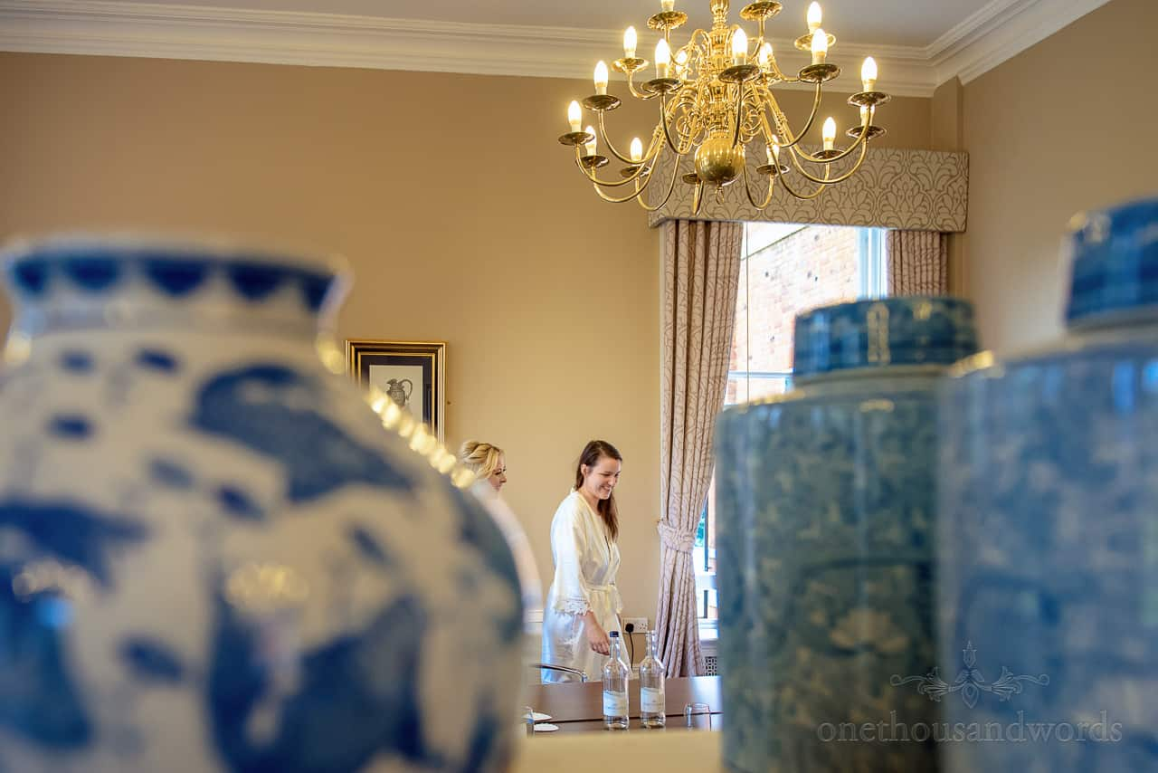 Happy bride on wedding morning at oakley Hall reflected in mirror with chandelier