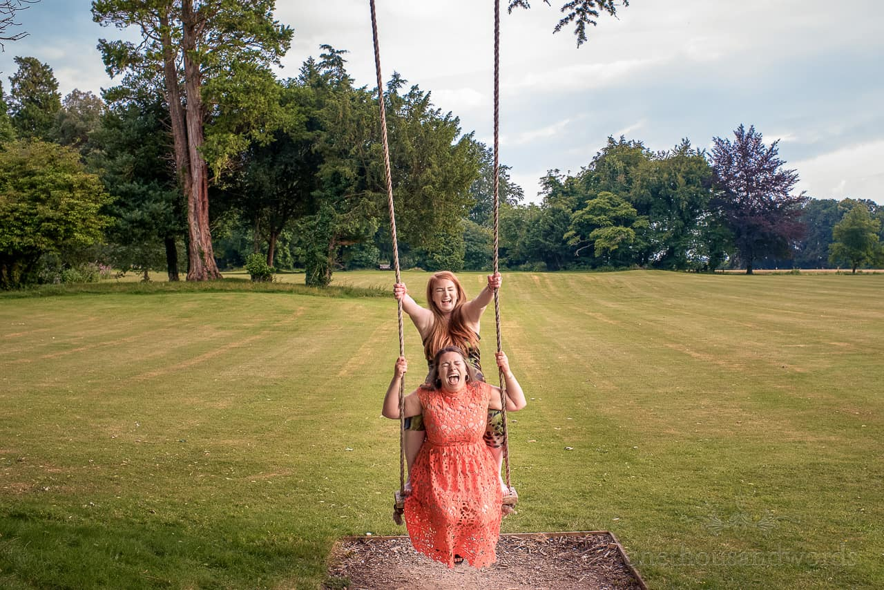 Hilarious laughing guests in tree swing at Oakley Hall gardens