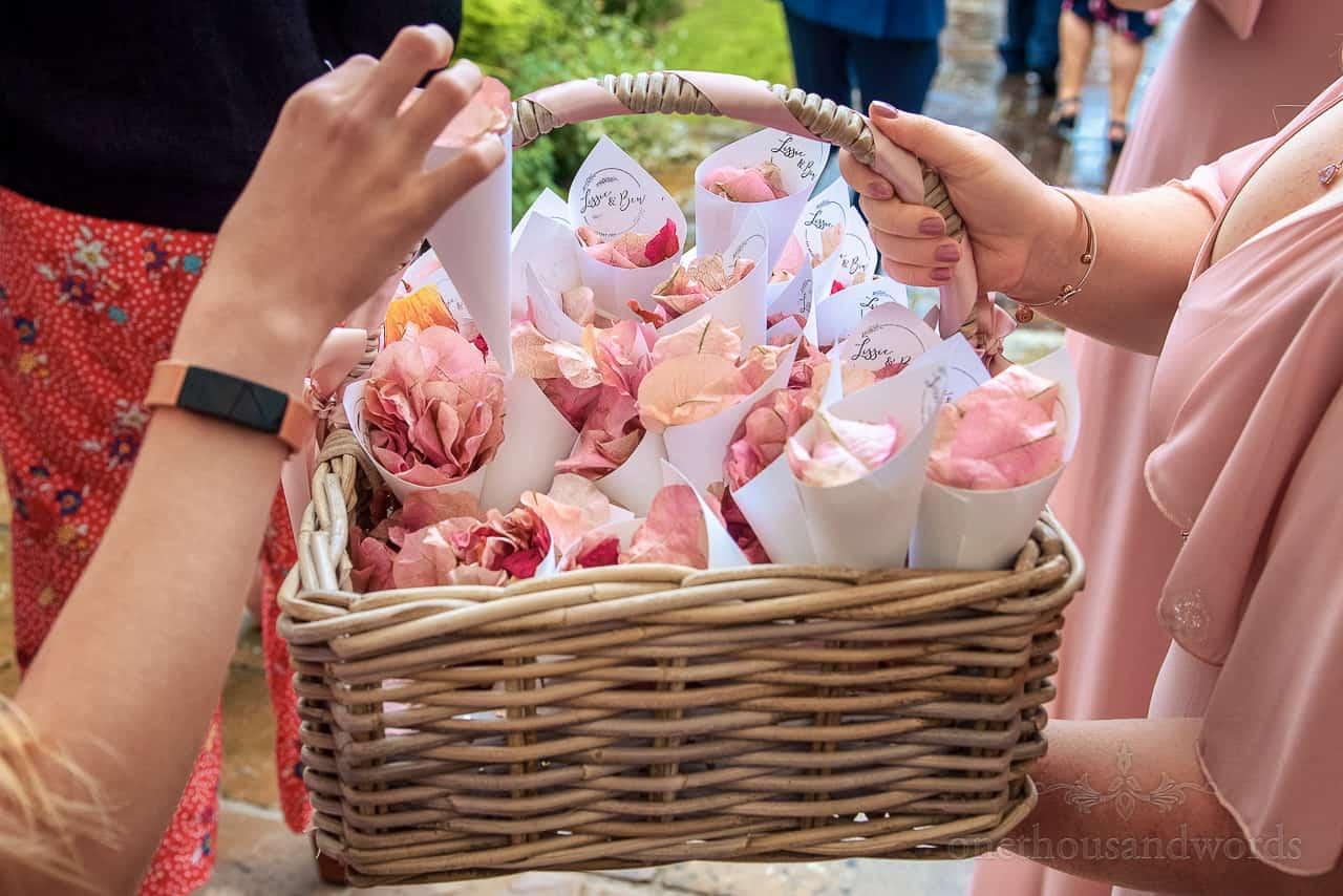 Home made pink wedding confetti cones in wicker basket photo