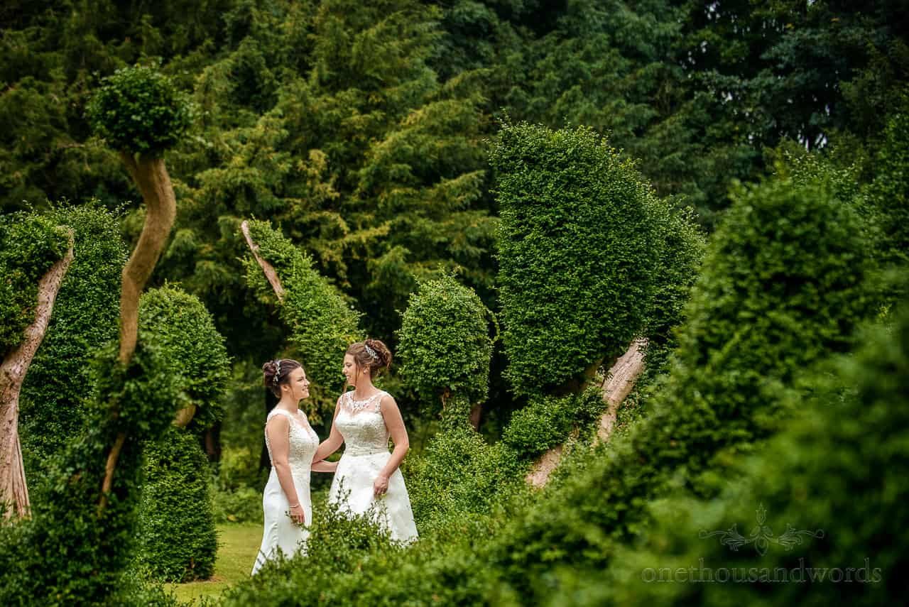 An intimate moment between two brides in topiary gardens at Oakley Hall wedding venue photographs