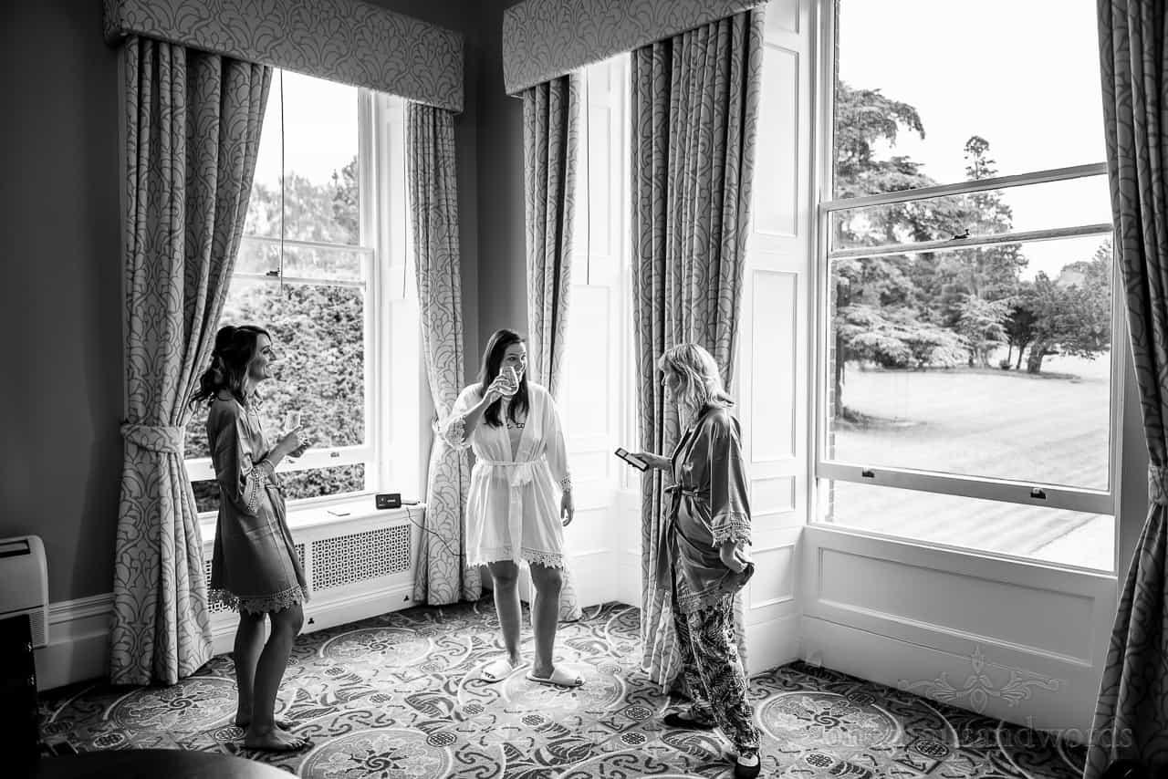 Laughing bride and bridesmaids at Oakley Hall windows during bridal preparations