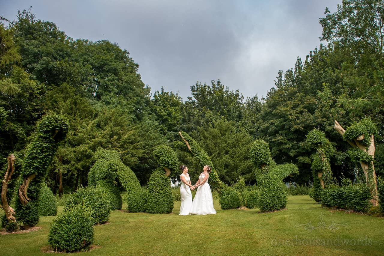 Laughing brides in white dresses hold hands in Oakley Hall Gardens