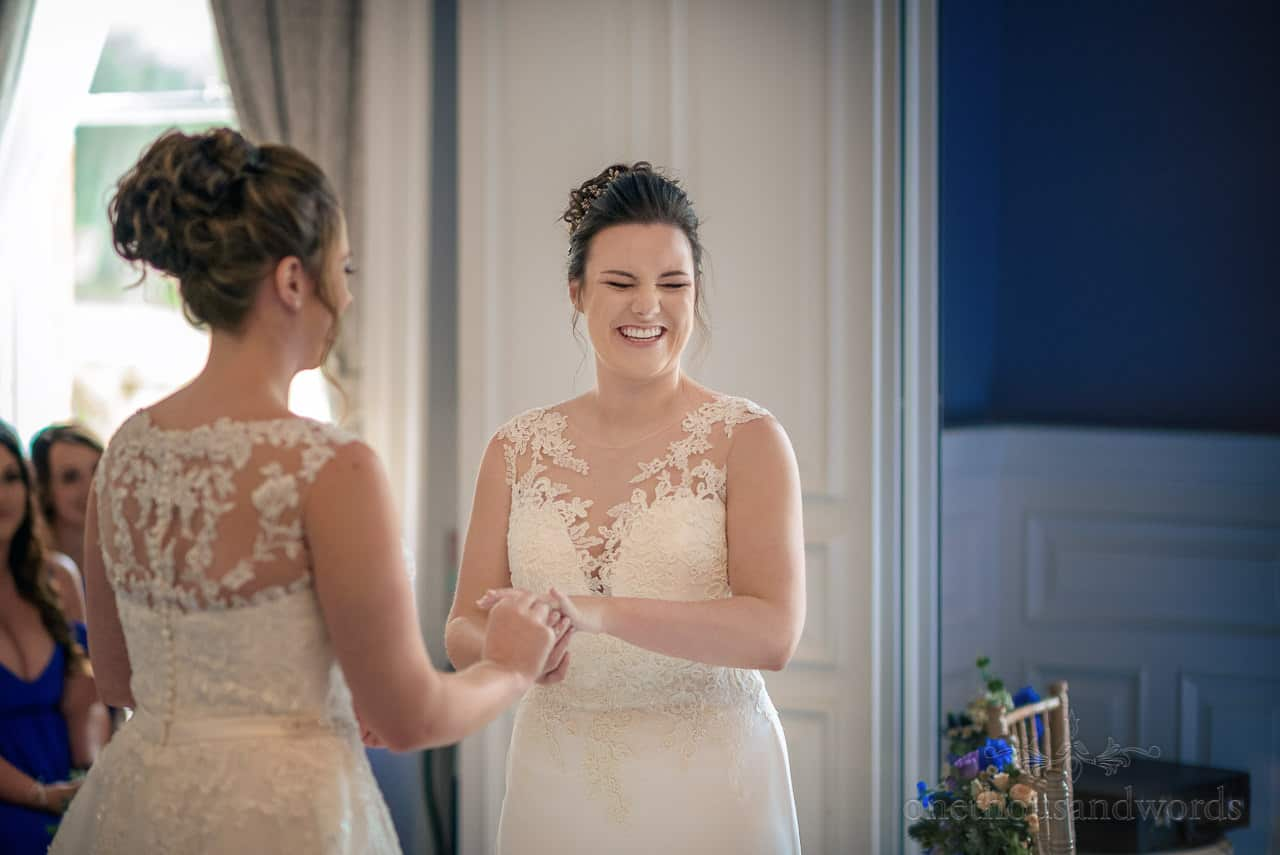Laughing brides in white dresses hold hands during civil wedding ceremony