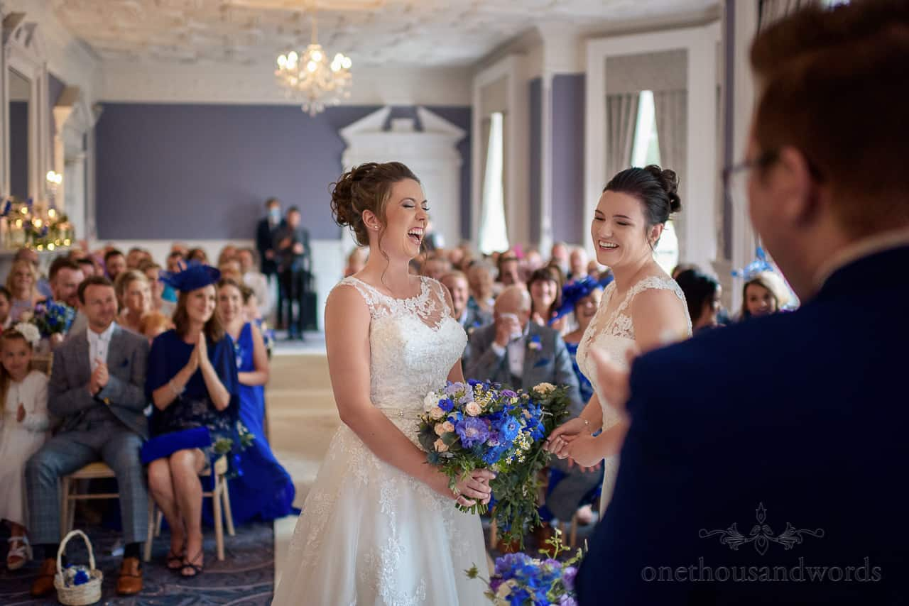 Laughing brides in white wedding dresses at Oakley Hall wedding ceremony photo