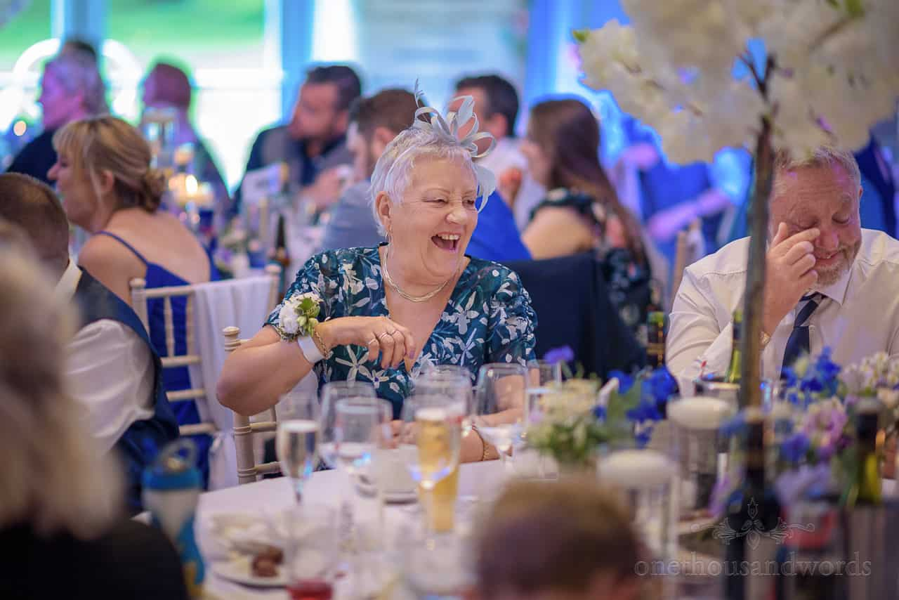Laughing elderly wedding guests in marquee react to wedding speeches