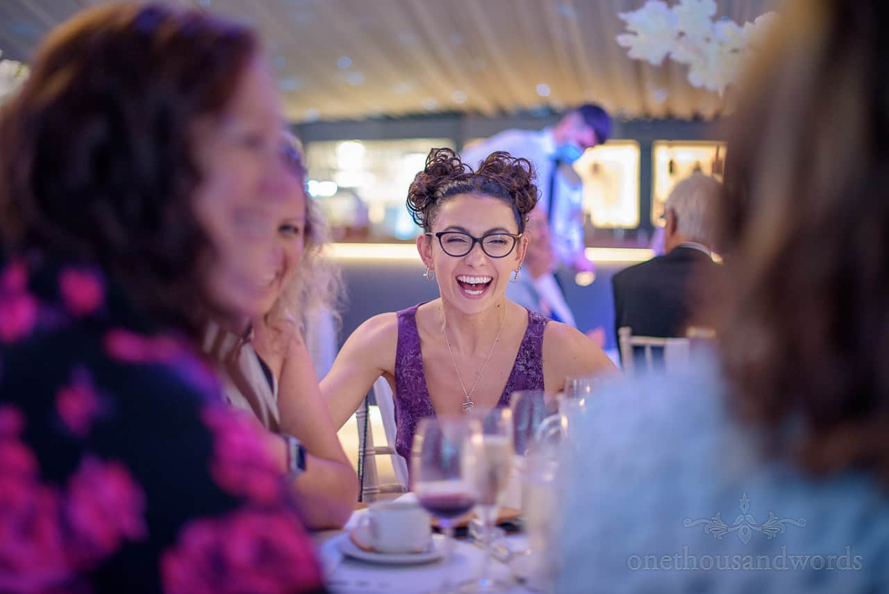Laughing wedding guest with space buns hairstyle at wedding marquee breakfast