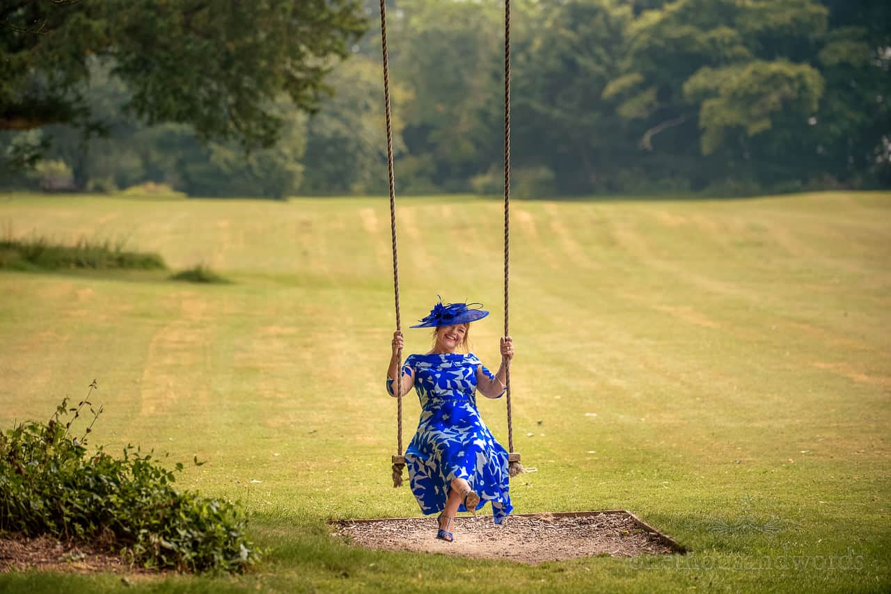 Mother of the bride wearing blue dress and hat smiles in tree swing on Oakley Hall gardens
