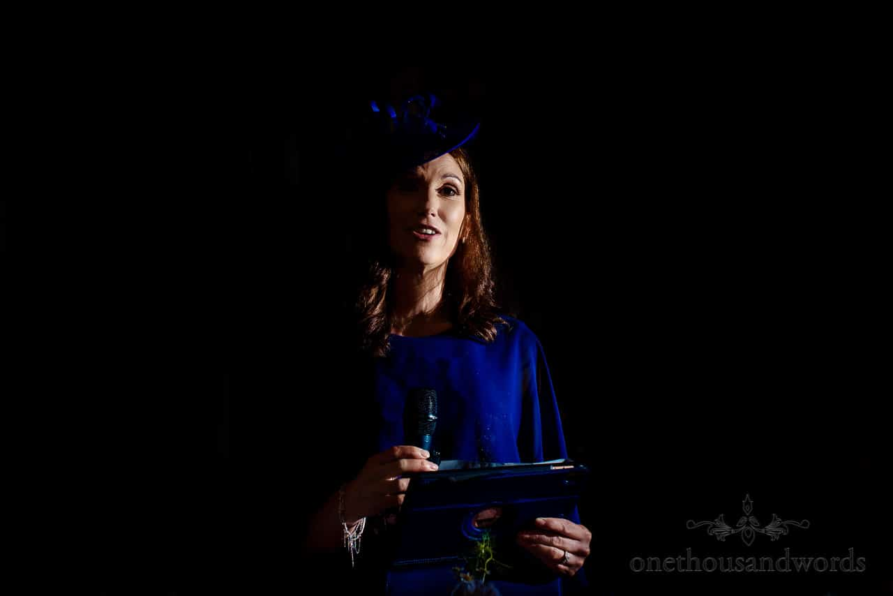 Mother of the bride in blue dress and fascinator gives wedding speech with microphone and ipad