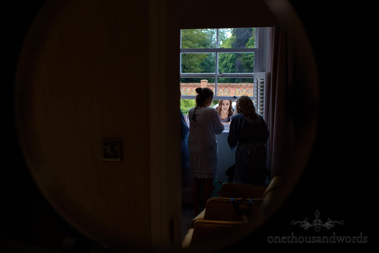 Mother of bride checks in on the bridal suite wedding morning through a sash window
