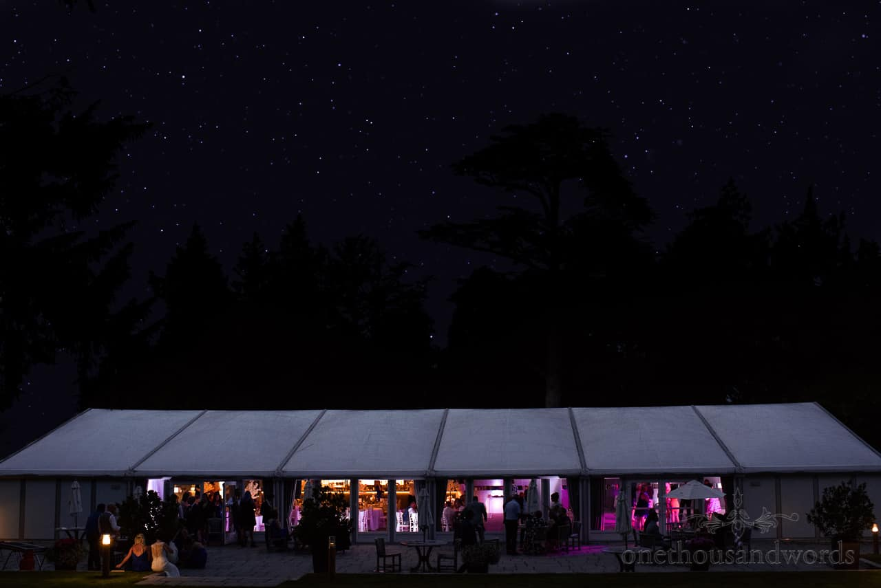 Oakley Hall wedding photos of pavillion marquee glowing at night with starry sky and tree silhouettes