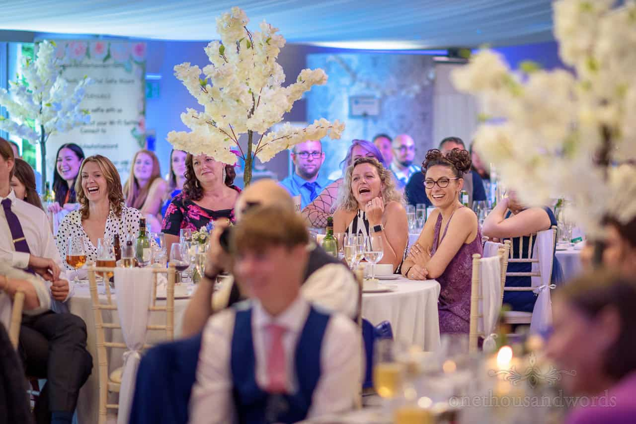 Oakley Hall wedding pavillion marquee guests laughing at speeches with white trees on tables