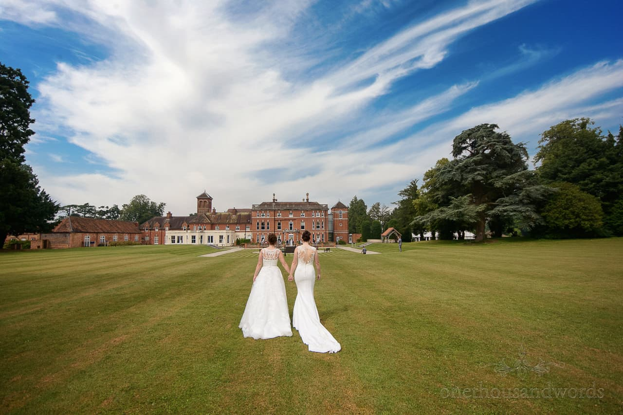 Oakley Hall wedding photos with two brides walking hand in hand through green lawns with blue sky