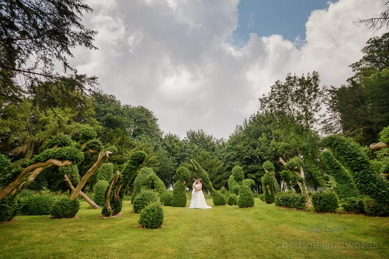 Oakley Hall wedding venue in Hampshire photographs of brides kissign in gardens with topiary