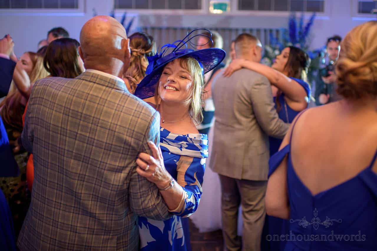 Mother of bride in blue dress and hat dancing at marquee wedding