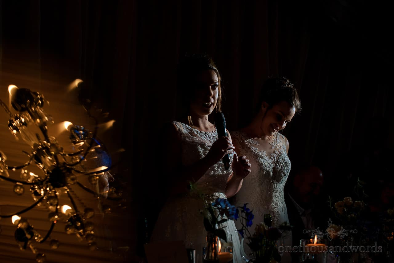 Same sex brides make wedding speeches with microphone and chandelier reflection